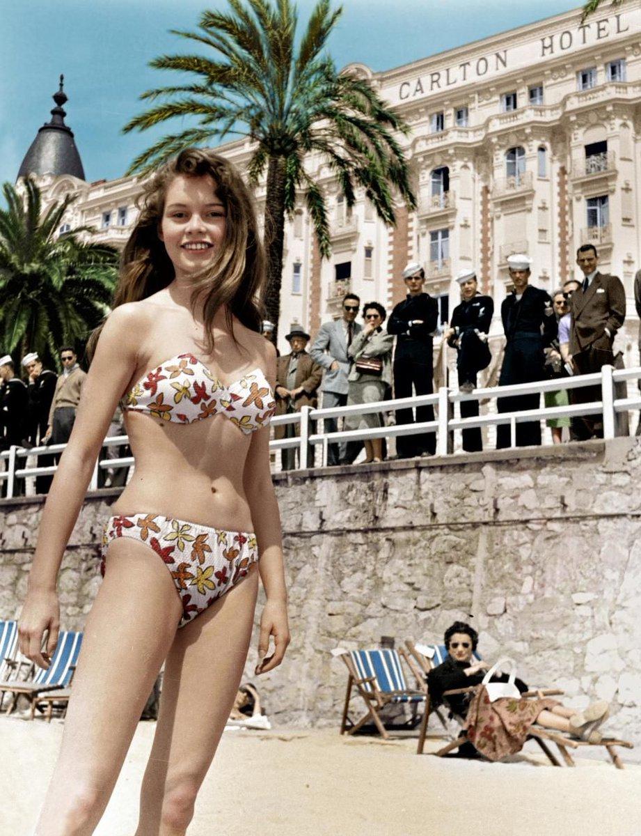 Người đẹp Brigitte Bardot tươi tắn trên bãi biển Cannes, tại sự kiện LHP Cannes năm 1956, trong thiết kế bikini in hoa trẻ trung.