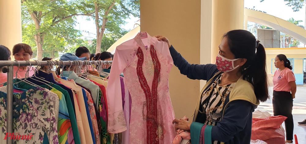 Tại gian hàng tặng áo dàii, các chị nữ công chọn cho mình một bộ áo dài để mặc trong những dịp đặc biệt