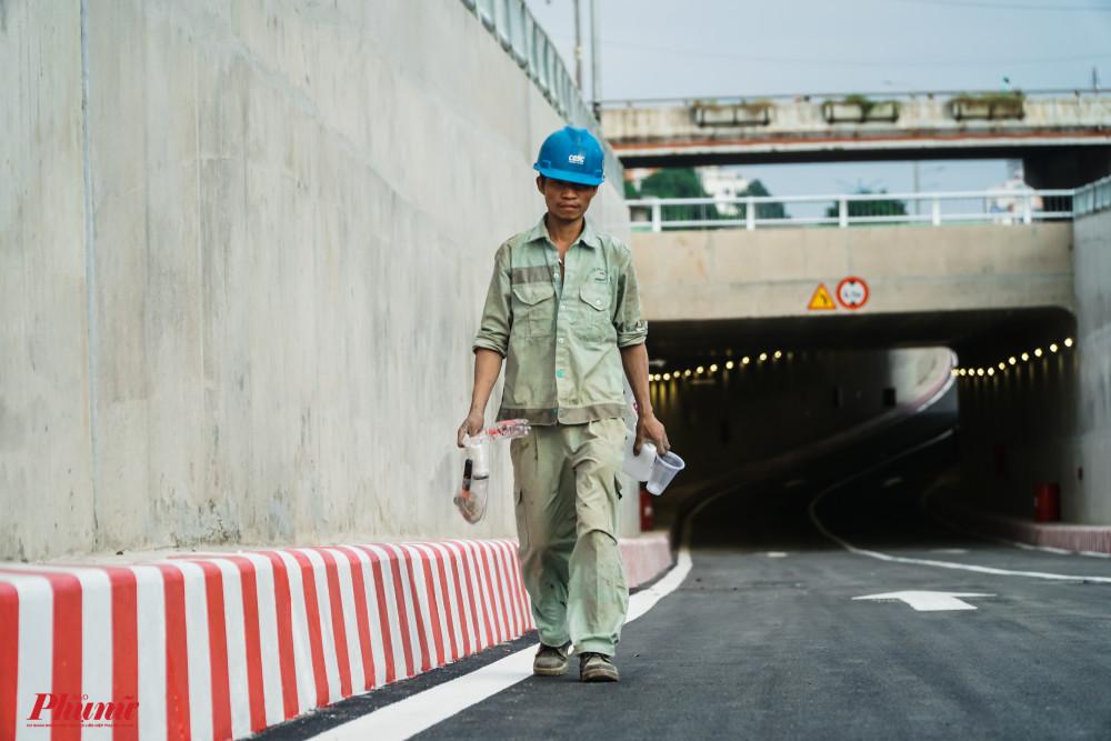 Các công nhân đang hoàn tất các công đoạn cuối cùng - Hình ảnh người công nhân đang dọn rác sạch sẽ trước giờ con đường được thông xe