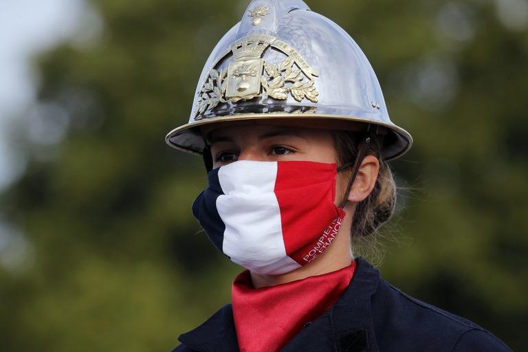 Lính cứu hỏa mang khẩu tranh màu cờ Pháp trong ngày quốc khánh - Ảnh: AP