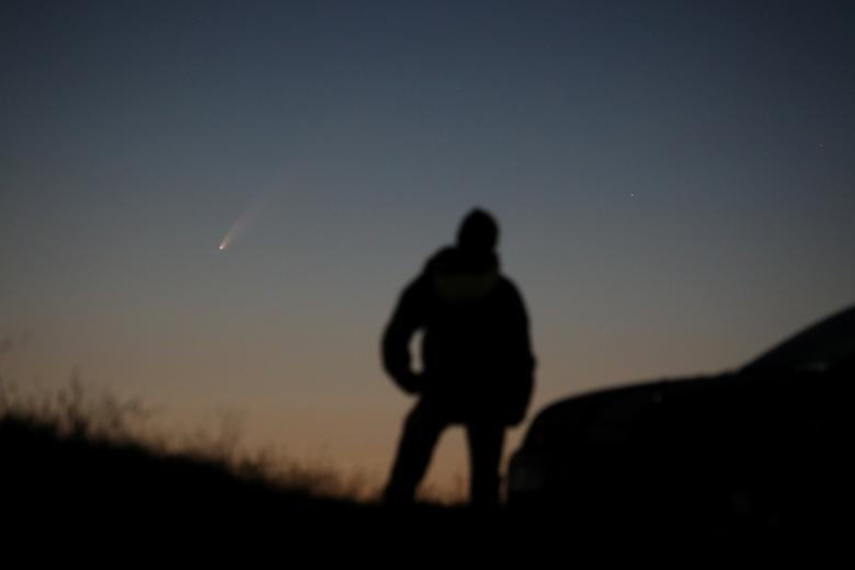 Một người đàn ông đứng quan sát sao chổi C/2020 ở Ballintoy, Anh. Khoảng giữa tháng 7, sao chổi này sẽ xuất hiện ở vị trí khoảng 10 độ trên đường chân trời phía đông bắc trong vòng một giờ trước khi bình minh.