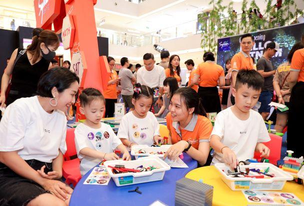 Các con của Ốc Thanh Vân đam mê tham gia trải nghiệm nhận sticker dán đầy áo tại ngày hội Sylvan Learning Việt Nam