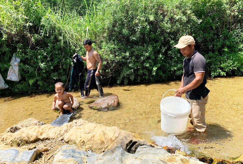Từ sáng sớm, người dân các xã vùng cao H.Nam Đông phải ra tận suối để lấy nước về dùng - Ảnh: THUẬN HÓA