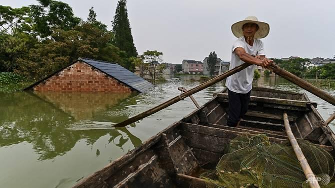 Người đàn ông chèo thuyền đi qua mái nhà bị ngập tại khu vực hồ Bà Dương