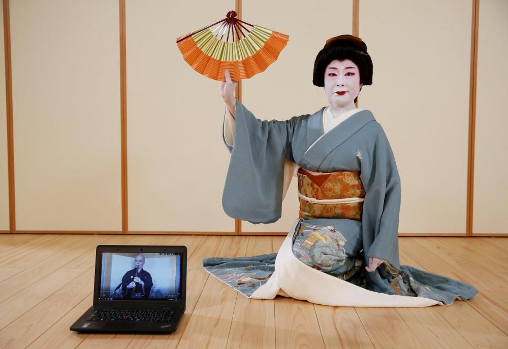 Tokijyo Hanasaki, một vũ công jiutamai, chụp ảnh đằng sau chiếc laptop trong một buổi trình chiếu nhằm hỗ trợ gây quỹ cho các nghệ sĩ trong đợt bùng phát dịch bệnh.