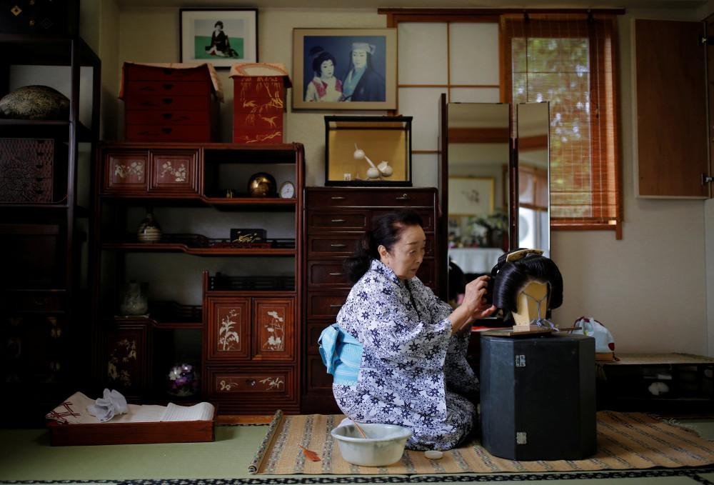 Ikuko, một geisha lão luyện, chải tóc giả trong phòng khách khi cô ấy chuẩn bị làm việc tại một bữa tiệc tổ chức ở một nhà hàng sang trọng.