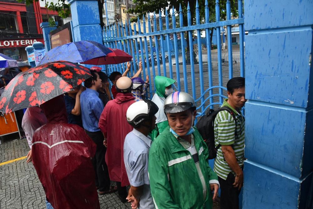 Phụ huynh đội mưa chờ con trước cổng trường thi. Ảnh minh hoạ
