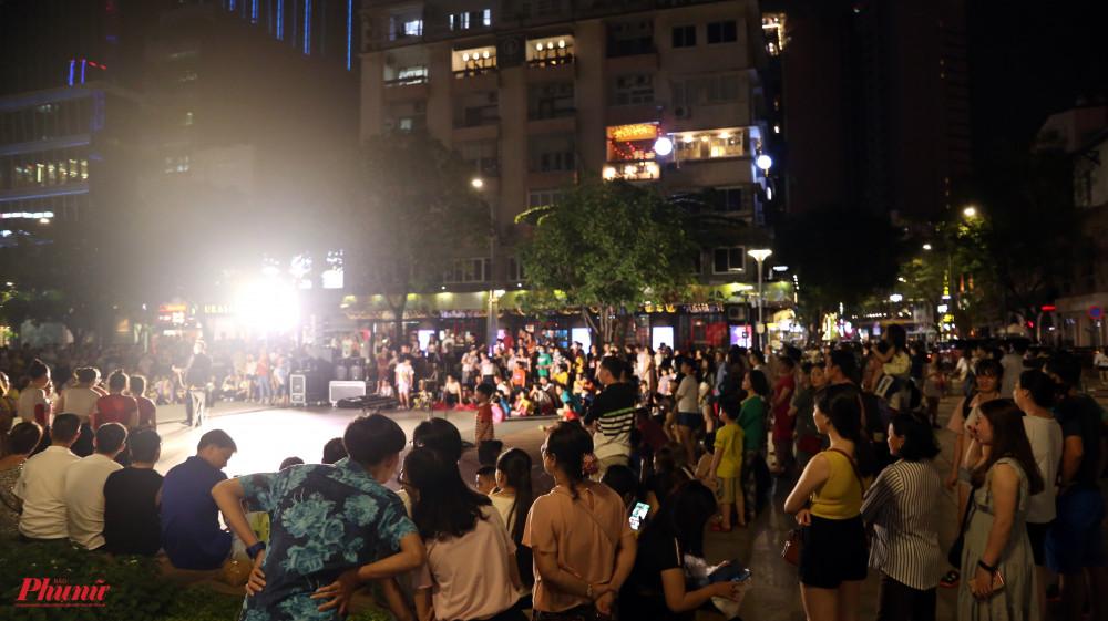 Nhóm khán giả đứng, ngồi thành một vòng tròn xung quanh sân khấu ngoài trời của nghệ sĩ. Sân khấu hình tròn thử thách các nghệ sĩ trong việc linh động tương tác với khán giả.