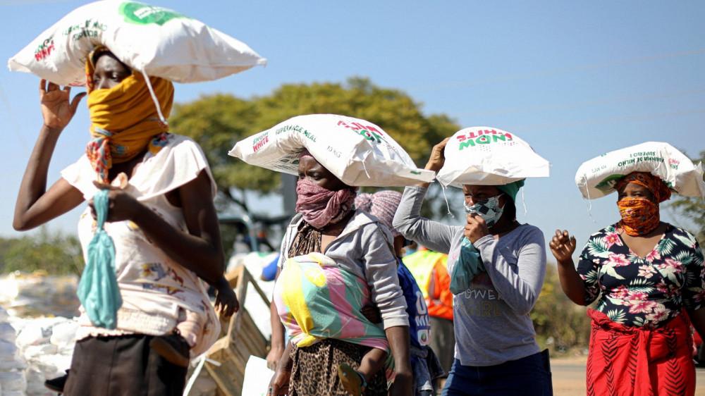 Phụ nữ nhận những túi bắp từ chương trình viện trợ lương thực, diễn ra gần Pretoria, Nam Phi - Ảnh: Reuters