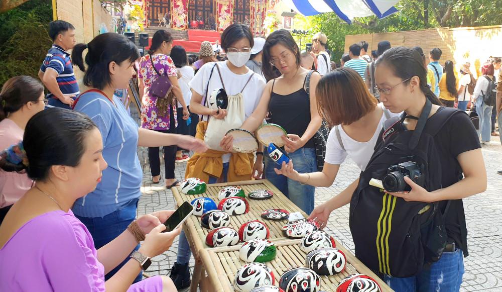 khán giả trẻ thích thú chọn mua mặt nạ hát bội vẽ trên gáo dừa