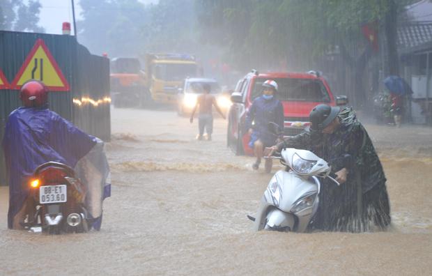 Người dân đi lại vô cùng khó khăn do mưa và ngập lụt.