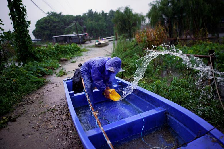 Một người đàn ông tranh thủ tát nước bên trong thuyền cao su để di chuyển khỏi khu vực ngập úng.