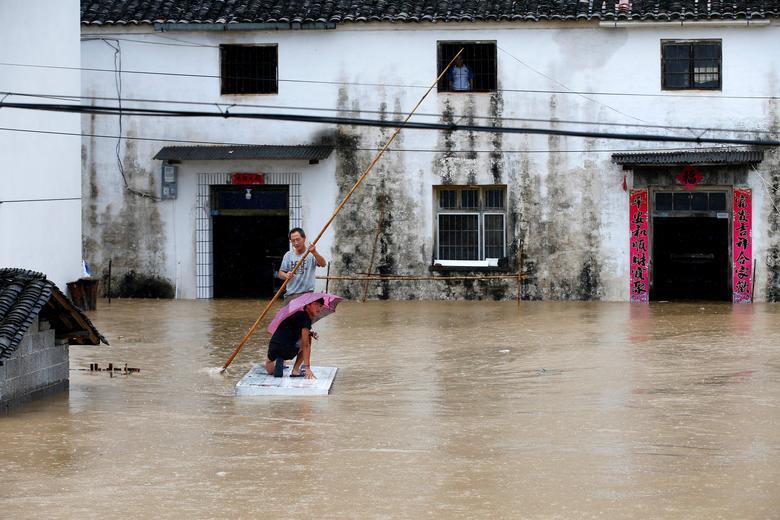 Người dân trong một ngôi làng ở tỉnh An Huy tận dụng đồ đạc trong nhà để làm một chiếc bè di chuyển giữa dòng nước lũ.