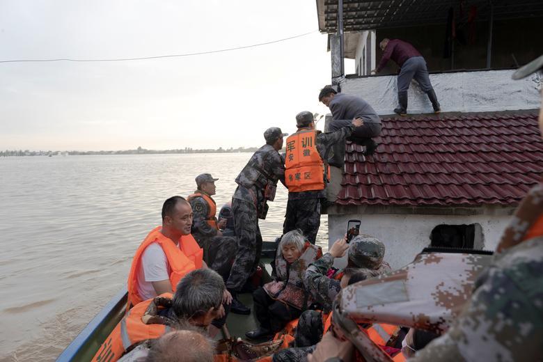 Có nơi, nước ngập gần mái nhà. Lực lượng cứu hộ phải trèo lên cao để sơ tán người dân.