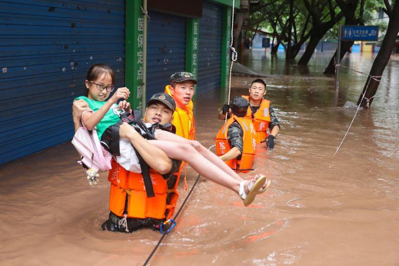 Lực lượng cứu hộ sơ tán một học sinh tiểu học tại Vạn Châu, Trùng Khánh hôm 16/7.