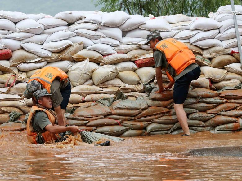 Lực lượng quân đội dùng bao cát để ngăn dòng nước tràn vào một ngôi làng ở Hồ Bà Dương, tỉnh Giang Tây, Trung Quốc.