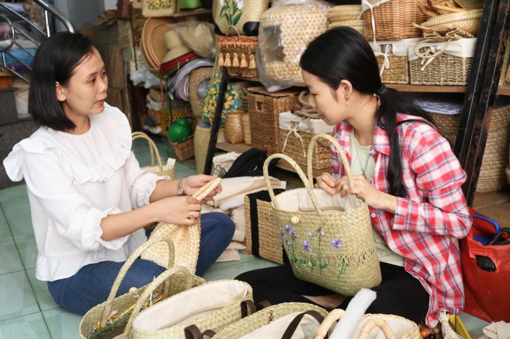 Chị Thu Hương hướng dẫn công nhân làm quai túi xách tre thời trang tại cơ sở mây tre lá  Dạ Lý Hương