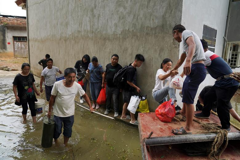 Người dân xếp hàng để chờ đến lượt lên thuyền cứu trợ tại tỉnh Giang Tây hôm 16/7.
