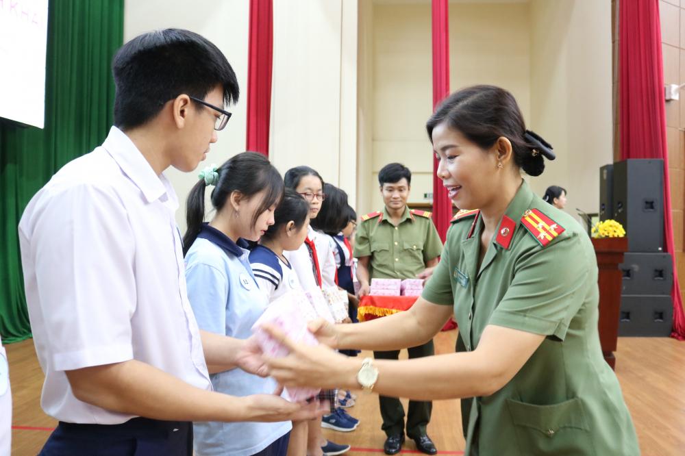 Thượng tá Cao Thị Hồng Tươi - Chủ tịch Hội Phụ nữ Công an TP.HCM trao học bổng cho các em học sinh.