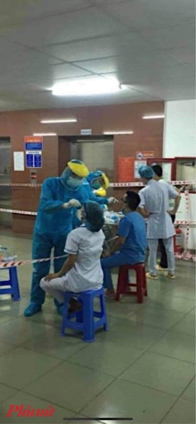 Các nhân viên y tế của bệnh viện C tiếp xúc gần với nam bệnh nhân được lấy mẫu xét nghiệm COVID-19