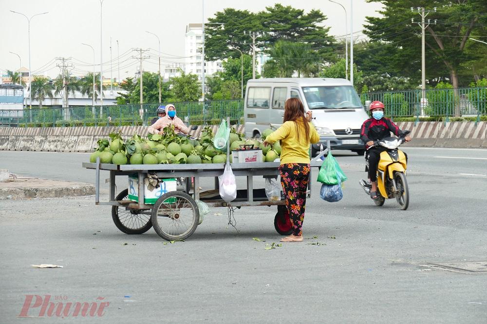 3. Bất chấp nguy hiểm, một người phụ nữ kéo xe bưởi ra giữa ngã tư để chào mời khách mua. Ghi nhận của phóng viên, dù các tuyến đường này thường xuyên bị tắc nghẽn nhưng không hề có lực lượng Cảnh sát giao thông làm nhiệm vụ trên đường.