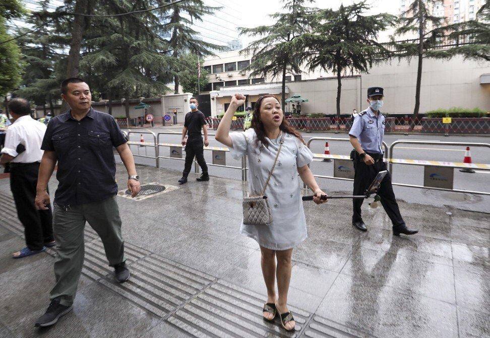 Cảnh sát yêu cầu một phụ nữ rời đi sau khi cô bắt đầu hát một bài hát yêu nước bên ngoài LSQ Mỹ - Ảnh: Simon Song