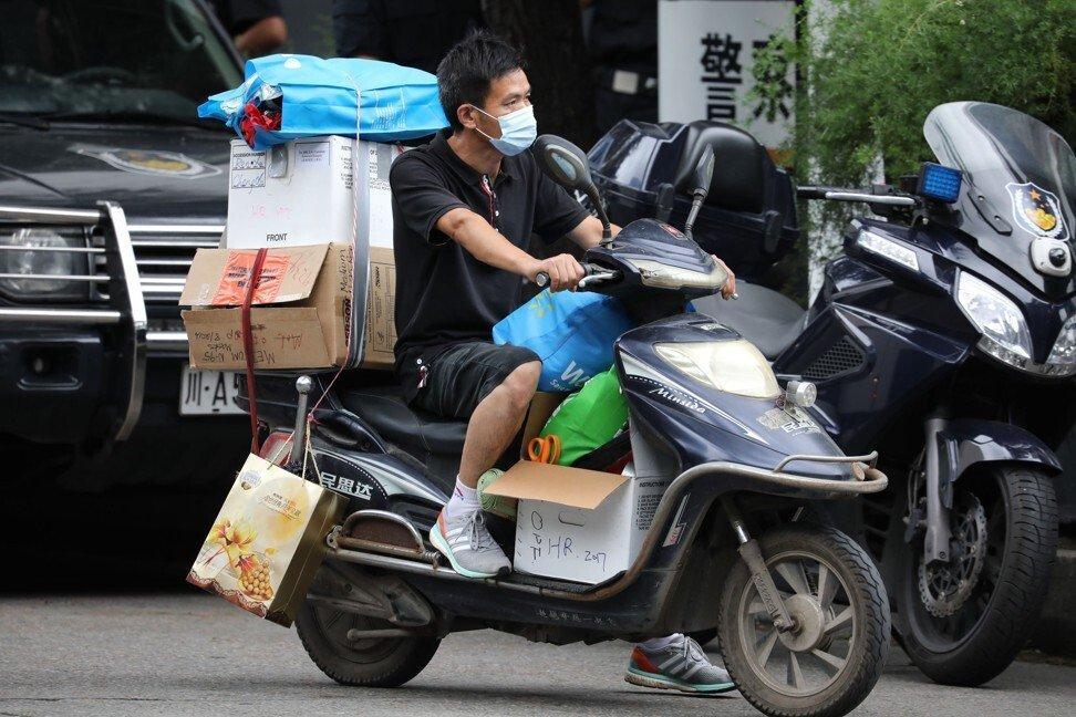 Một người đàn ông rời khỏi lãnh sự quán sáng 25/7 - Ảnh: Simon Song