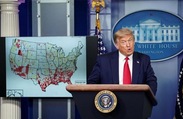 Tổng thống Donald Trump đứng cạnh bản đồ các trường hợp nhiễm COVID-19 tại Mỹ khi ông nói về kế hoạch mở lại trường học của chính quyền trong một cuộc họp báo về bệnh tại Nhà Trắng ở Washington, ngày 23/7.