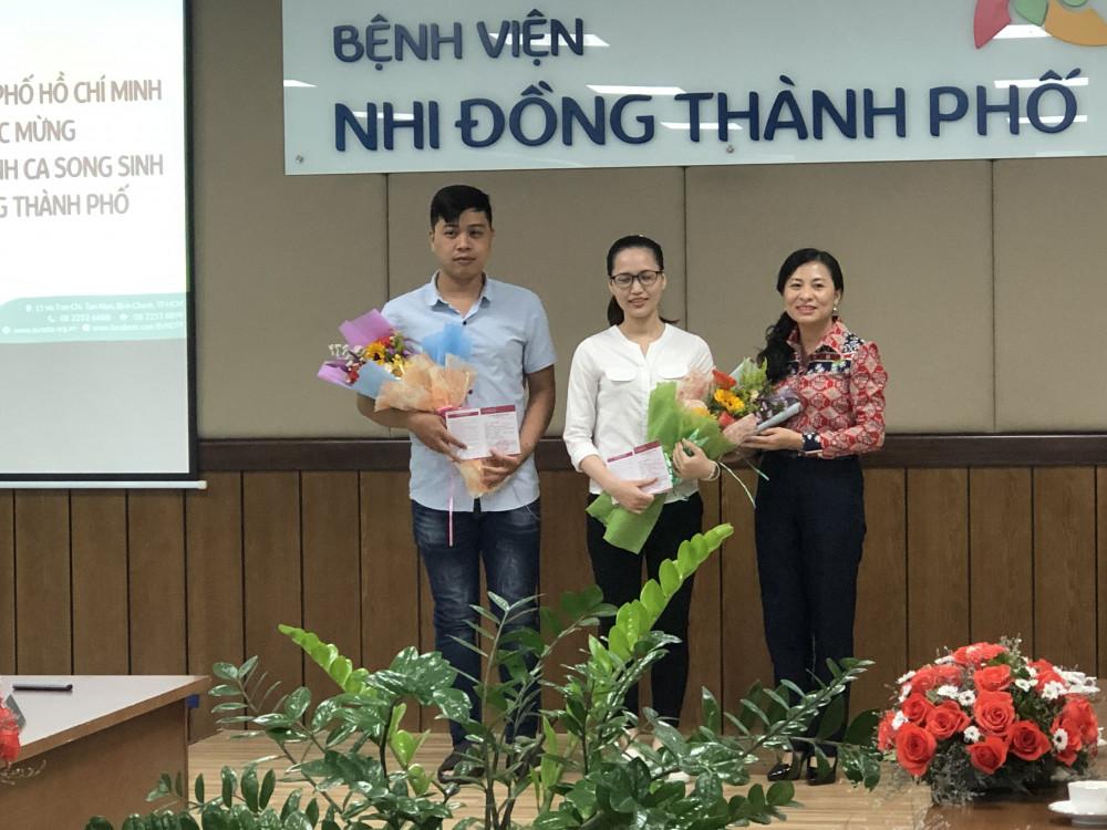 Trao tặng hai sổ tiết kiệm cho cha mẹ của bé Trúc Nhi, Diệu Nhi.