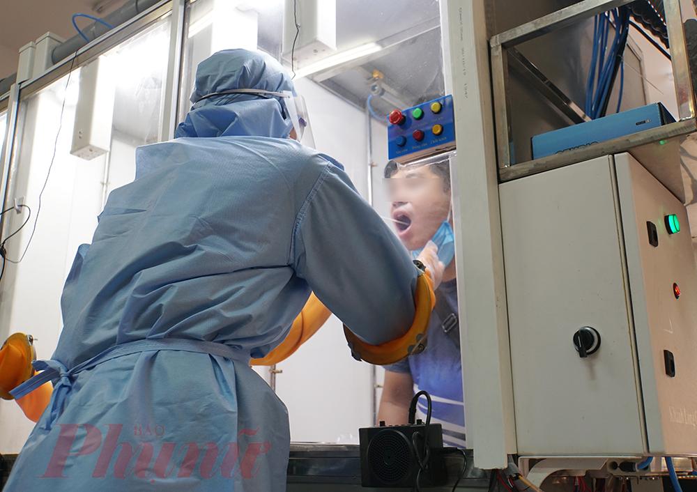 Nhân viên y tế của Bệnh viện Quận 2 lấy mẫu xét nghiệm cho người dân bằng cabin di động.