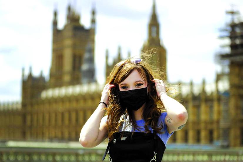 """Estelle Fitz tạo dáng trên cầu Westminster ở London (Anh). Cô nói: """"Bạn nên đeo khẩu trang vì sự an toàn của mọi người, tôi chắc chắn đó là lý do lớn nhất cho điều đó. Bạn phải nghĩ về những người khác"""" - Ảnh: AP"""