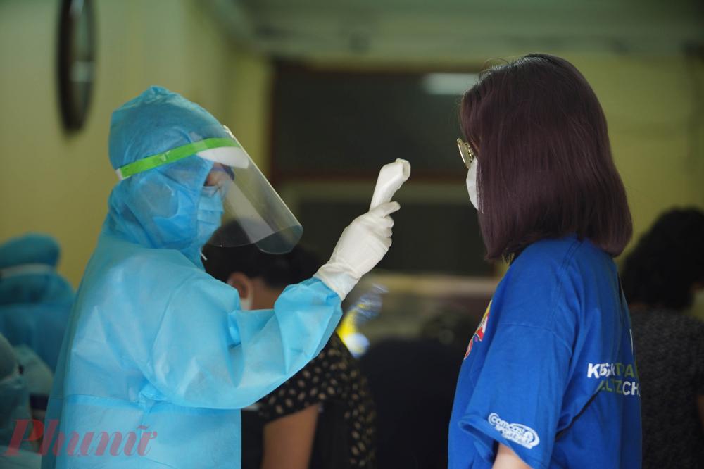 Người dân trước khi vào khu vực khai báo y tế sẽ được đo thân nhiệt và kiểm tra các biểu hiện bệnh.