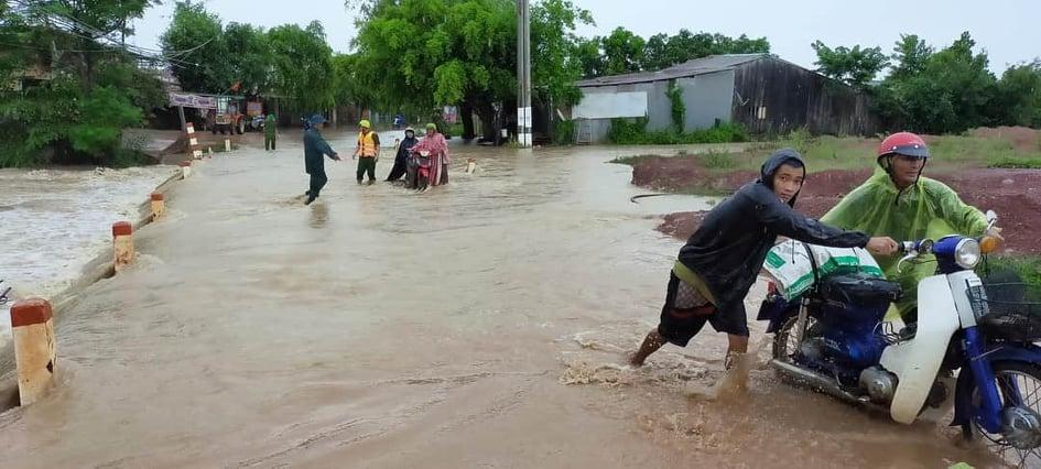 Lực lượng chức năng hỗ trợ người dân đi qua các đoạn đường ngập lụt