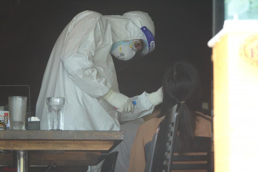 Lực lượng chức năng lấy mẫu dịch hầu họng tại địa điểm có bệnh nhân mắc COVID-19 làm việc