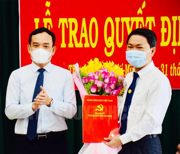 Phó Bí thư Thường trực Thành ủy TP.HCM Trần Lưu Quang trao quyết định và tặng hoa chúc mừng ông Trần Hoàng Quân. Ảnh: Web Thành ủy TP.HCM.