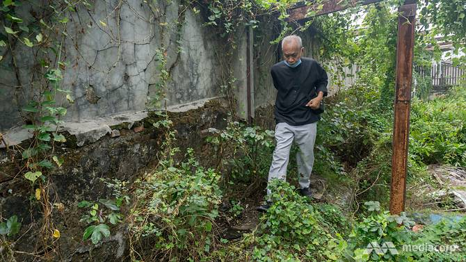 Nhà khảo cổ học Candrian Attahiyat đi dọc theo một phần bức tường vẫn còn tồn tại