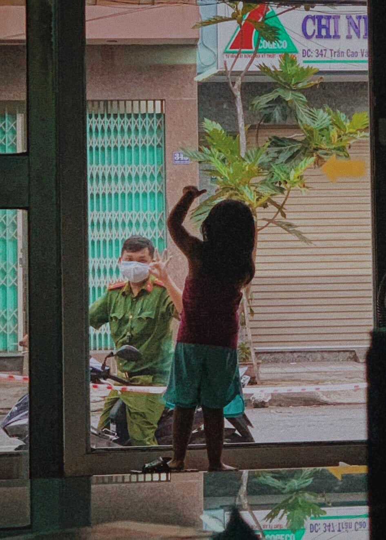 """Em bé thấy ba ngoài cửa nhưng không thể ôm hôn chuyện trò, hai cha con đành nhìn nhau qua tấm cửa kính. Bé đưa tay ra dấu """"Like"""" dễ thương và trìu mến với ba. Ảnh từ Facebook."""