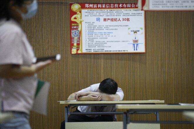 Một người tìm việc nghỉ ngơi ngay tại hội trường hội chợ tuyển dụng ở Trịnh Châu (Trung Quốc). Sinh viên trẻ mới ra trường phải đối mặt với thị trường việc làm hết sức khó khăn - Ảnh: AFP