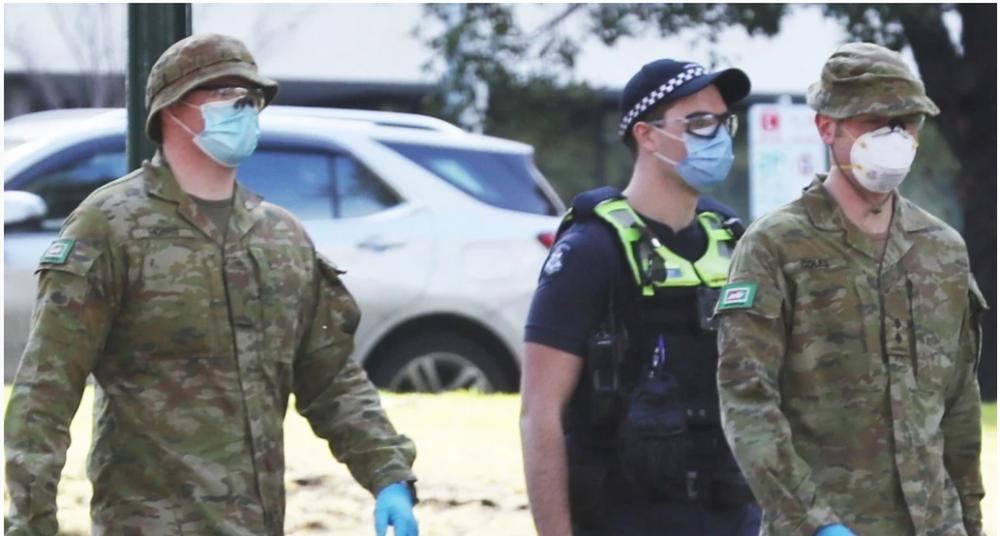 Nhân viên Lực lượng Quốc phòng Úc và cảnh sát Victoria tuần tra tại Melbourne, nơi lệnh giới nghiêm ban đêm đã được ban hành