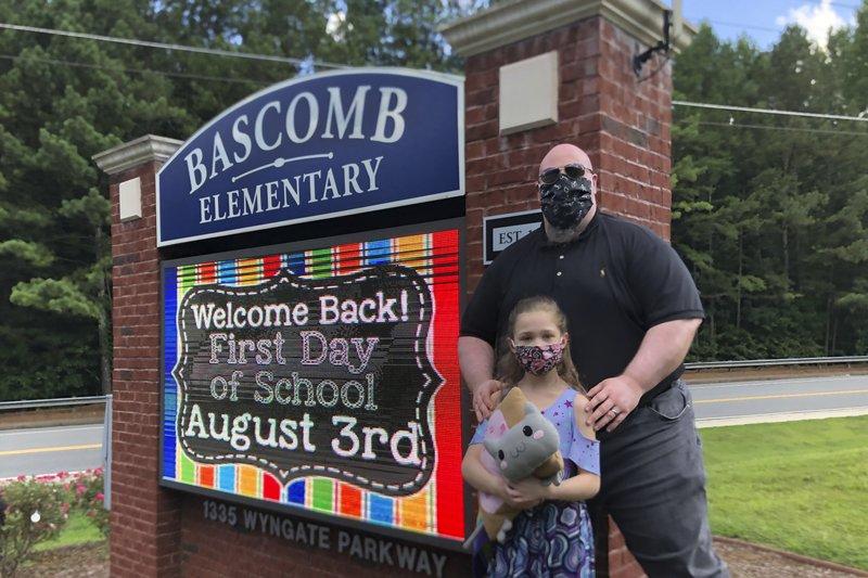 John Barrett và con gái Autumn bên ngoài Trường tiểu học Bascomb ở Woodstock, Georgia - Ảnh: AP