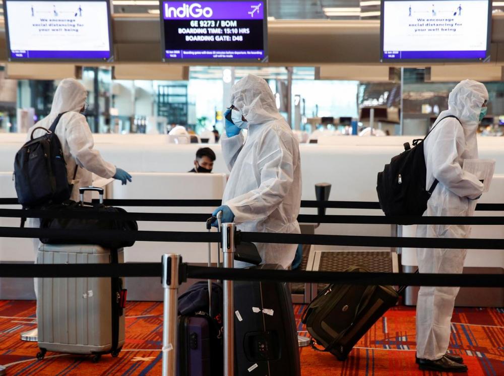 Các thủy thủ người Ấn Độ làm việc nhiều tháng trên tàu Singapore đến sân bay Changi làm thủ tục bay về nước - Ảnh: Reuters
