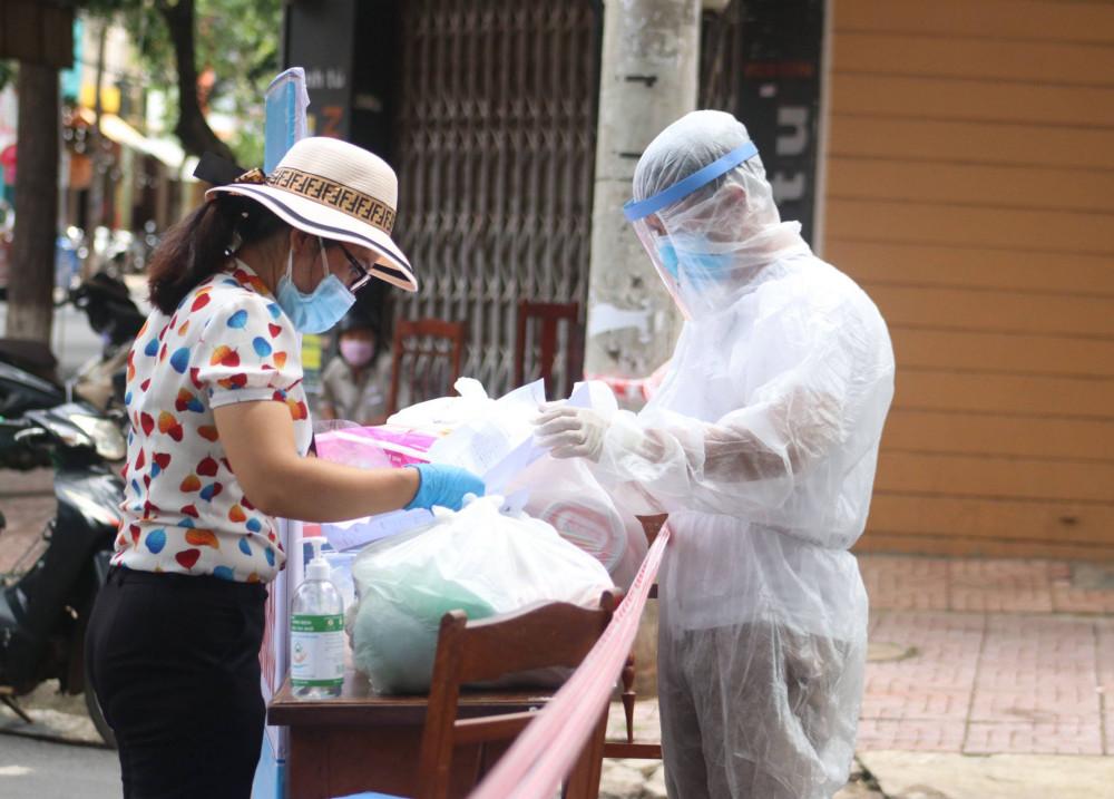 Sau khi đi chợ về, các cán bộ hội phụ nữ giao thưc phẩm cho cán bộ y tế tại khu vực cách ly để phát cho người dân
