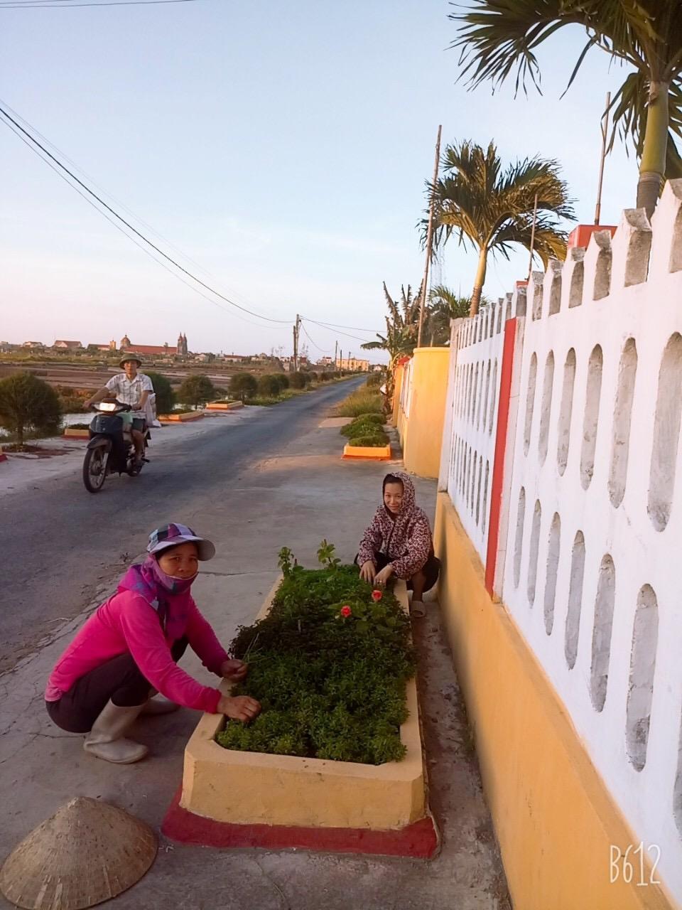 Chị Nguyễn Thị Tằm (bên trái) chăm sóc hoa kiểng trên tuyến đường của Xóm Trung Chính.