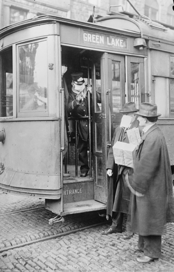 Người dân phải đeo khẩu trang trước khi lên xe điện ở Seattle năm 1918. Ảnh tư liệu