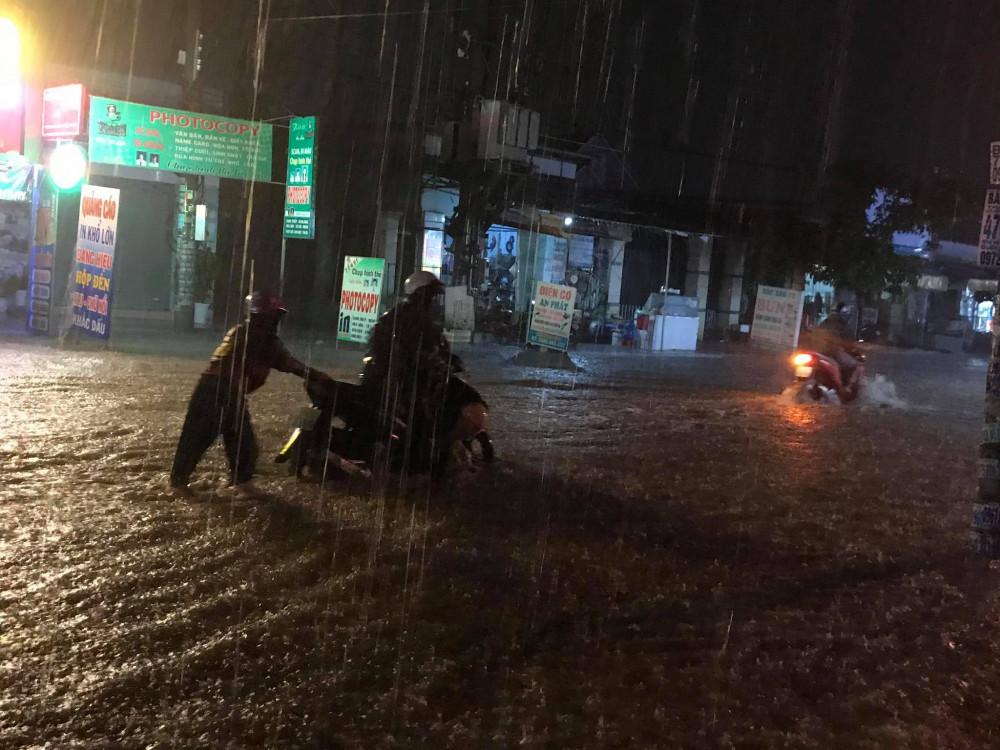 Người dân đẩy bộ xe máy qua vùng nước ngập do xe chết máy