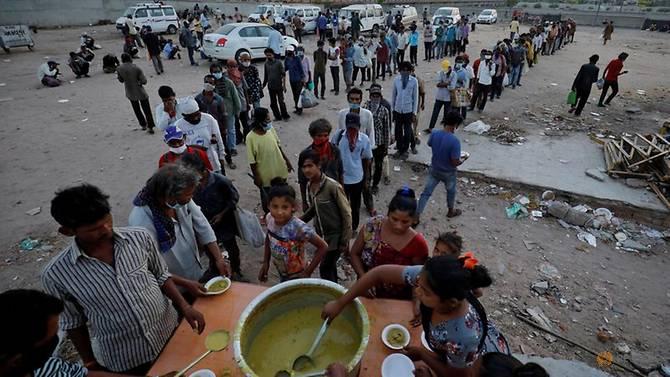 Người lao động nhập cư và người vô gia cư xếp hàng chờ nhận thức ăn miễn phí trong thời gian đất nước phong toả để ngăn chặn dịch bệnh