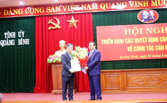 Ông Phạm Minh Chính - Trưởng Ban Tổ chức Trung ương trao quyết định, tặng hoa cho tân Bí thư Tỉnh ủy Quảng Bình Vũ Đại Thắng (trái)