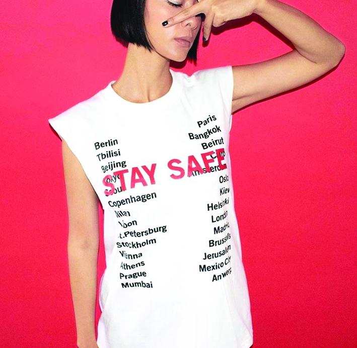 """Nhằm kêu gọi mọi người nên hạn chế ra ngoài, tránh lây lan vi-rút, các thương hiệu đã tung ra mẫu áo thun với thông điệp ý nghĩa như vậy. Chiếc áo thun có 2 kiểu dáng: 1 là kiểu  truyền thống, 1 là kiểu tank-top cực ngầu với 2 sắc màu  cơ bản trắng và đen. Trên áo thun có in tên các địa danh kèm theo dòng chữ màu đỏ nổi bật """"Stay Safe"""" - ngụ ý về việc mọi người ở mọi nơi trên thế giới nên thực hiện việc ở yên một chỗ"""