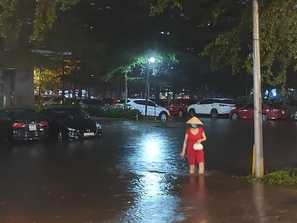Một người phụ nữ đi mua đồ ăn khuya trở về nhà phải lội nước ngập gần đến đầu gối.