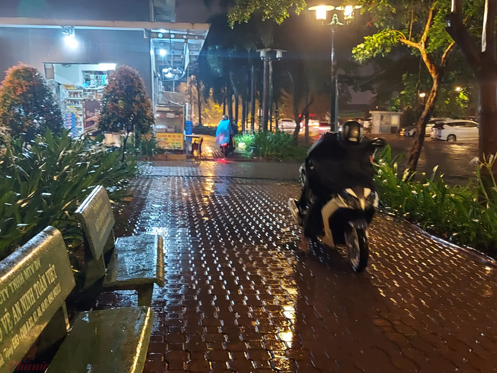 Một cư dân di chuyển qua nước ngập xe bị chết máy nên phải leo lên vỉa hè đẩy bộ.